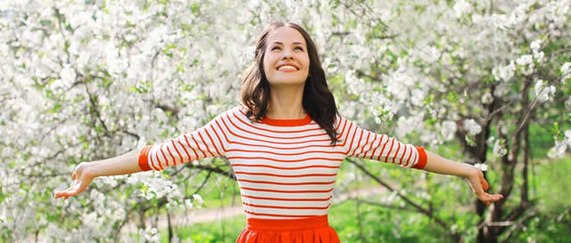 Grass is Greener - Confident young lady with outstretched arms in park