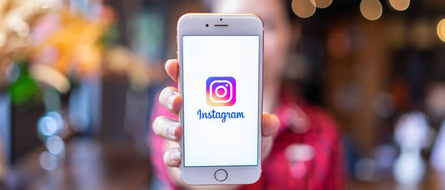 Lady holding out smartphone with Instragram logo display