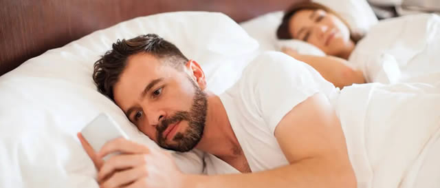 Social media usage - Man in bed with wife using smartphone